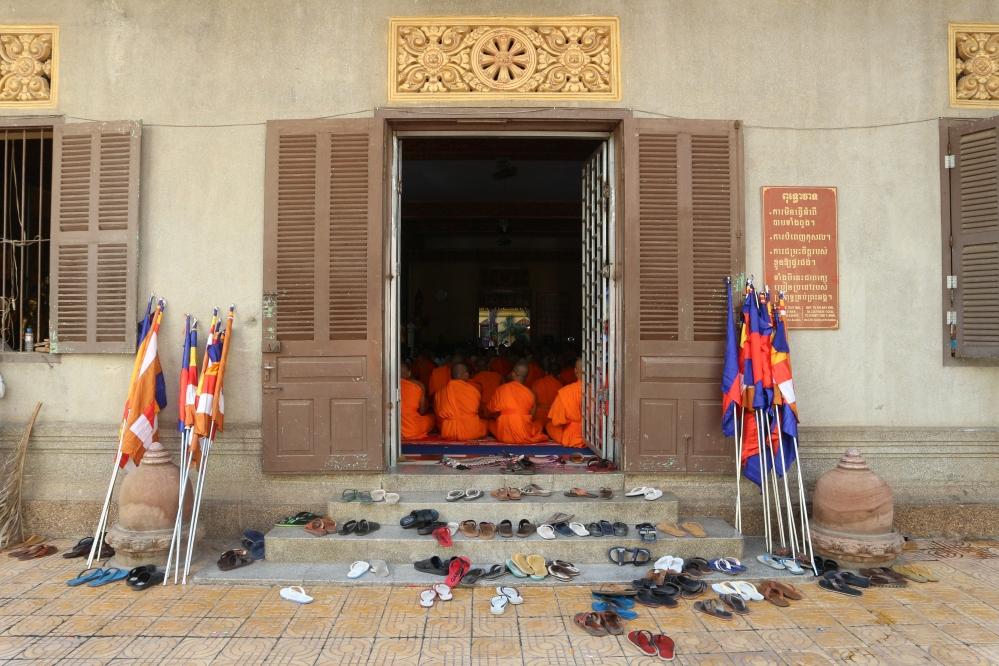 Wat Ounalum. Ceremonia budista. Los monjes se quitan sus zapatos para entrar en el templo.